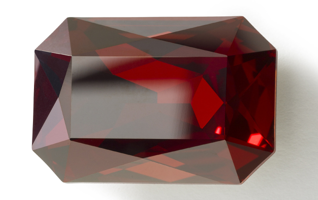 Close up of red crystal with precisely cut facets.